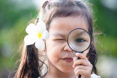 Nettes asiatisches kleines Kindermädchen, das durch eine Lupe schaut Stockfotografie
