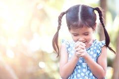 Nettes asiatisches kleines Kindermädchen, das mit gefaltet ihrer Hand betet lizenzfreie stockfotografie
