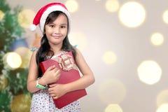 Nettes asiatisches kleines Mädchen mit Sankt-Hut, der Weihnachtsgeschenkbox hält stockfotografie