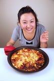Nettes asiatisches Mädchen, das eine Pizza anhält Lizenzfreies Stockbild