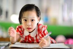 Nettes asiatisches Mädchen, das ihre Hausarbeit tut Lizenzfreies Stockbild