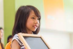 Nettes asiatisches Mädchen, das leere Tafel mit glücklichem Gesicht im Kindergartenklassenzimmer, Kindergartenbildungskonzept häl Lizenzfreies Stockfoto