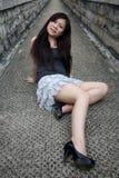 Nettes asiatisches Mädchen, das sich hinsitzt stockfoto