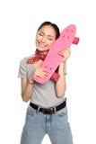 Nettes asiatisches Mädchen, welches das Skateboard lokalisiert auf Weiß umarmt Stockfotografie