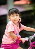 Nettes asiatisches Mädchenfahrfahrrad Stockfotos