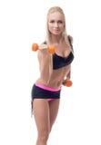 Nettes athletisches blondes Trainieren mit Dummköpfen Lizenzfreie Stockfotografie