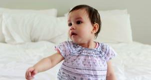 Nettes Baby, das auf Bett sitzt stock video