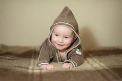 Nettes Baby, das auf dem Bett spielt, zur Kamera lächelt und aufwirft lizenzfreies stockbild