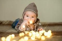 Nettes Baby, das auf dem Bett spielt, zur Kamera lächelt und aufwirft stockfotos