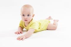 Nettes Baby, das auf dem Hintergrund und dem Lächeln liegt Lizenzfreie Stockfotos