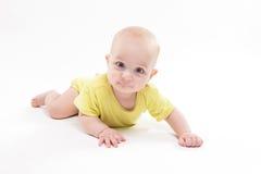 Nettes Baby, das auf dem Hintergrund und dem Lächeln liegt Stockfotografie