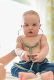 Nettes Baby, das auf ein Stethoskop hört Stockbilder