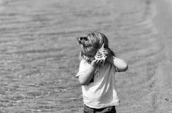 Nettes Baby, das auf Muschel auf Seestrand hört Stockfotografie