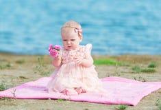 Nettes Baby, das auf sandigem Strand im rosa Kleid sitzt Stockbilder