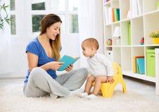 Nettes Baby, das auf Wärmflasche und hörender Kindergeschichte sitzt Stockfotos