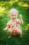 Nettes Baby, das auf Wiese mit Blume sitzt Lizenzfreie Stockfotos