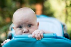 Nettes Baby, das aus einem Spaziergänger heraus späht Stockfotografie