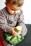 Nettes Baby, das Brokkoli in seinen Händen, zuhause sitzend auf dem Boden hält lizenzfreies stockfoto