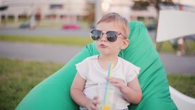Nettes Baby, das in der großen lustigen Sonnenbrille sitzt im Bohnentaschenstuhl am Park am Sommertag ist Halten eines Glases mit stock footage