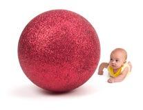 Nettes Baby, das eine enorme Weihnachtsverzierung auf Weiß betrachtet Stockfoto
