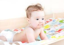 Nettes Baby, das in einem Bett trägt eine Windel spielt Lizenzfreie Stockfotos
