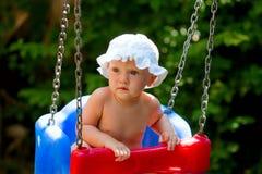 Nettes Baby, das in einem Schwingen sitzt Stockfotografie