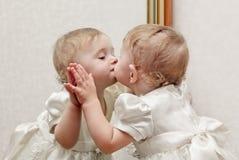 Baby, das einen Spiegel küsst stockbilder