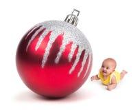 Nettes Baby, das an einer enormen Weihnachtsverzierung auf Weiß lächelt Stockbild