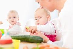 Nettes Baby, das gesundes festes Lebensmittel in einer modernen Kindertagesstätte isst stockbild