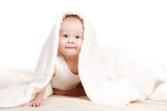 Nettes Baby, das heraus von unterhalb der Decke späht Lizenzfreie Stockfotos