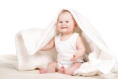 Nettes Baby, das heraus von unterhalb der Decke späht Lizenzfreie Stockbilder