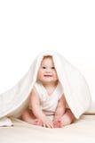 Nettes Baby, das heraus von unterhalb der Decke späht Lizenzfreies Stockfoto