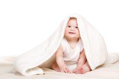 Nettes Baby, das heraus von unterhalb der Decke späht Stockfoto
