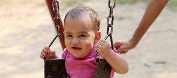 Nettes Baby, das im Park schwingt stockfotos