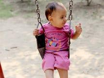 Nettes Baby, das im Park schwingt stockfoto