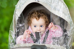 Nettes Baby, das im Spaziergänger unter Plastikregen sitzt Lizenzfreies Stockfoto