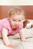 Nettes Baby, das Kamera auf Bett untersucht. Stockbild