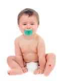 Nettes Baby, das mit Friedensstifter schreit Stockfoto