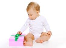 Nettes Baby, das mit Geschenkbox sitzt Stockbild