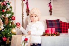 Nettes Baby, das mit neuem Year& x27 aufwirft; s-Ball in der Hand nahe Christma lizenzfreies stockbild