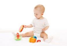 Nettes Baby, das mit Spielwaren auf Weiß spielt Lizenzfreie Stockfotografie