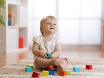 Nettes Baby, das mit Spielwaren im Wohnzimmer spielt stockbild