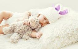 Nettes Baby, das mit Teddybärspielzeug auf weißem weichem Betthaus schläft Lizenzfreie Stockfotos
