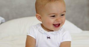 Nettes Baby, das mit Tuch auf Bett spielt stock video