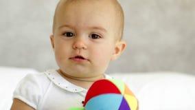 Nettes Baby, das mit weichem Ball auf Bett spielt stock video
