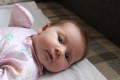 Nettes Baby, das oben auf weißen Bettlaken, Abschluss liegt Lizenzfreies Stockbild