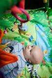 Nettes Baby, das oben Toy Frog betrachtet lizenzfreies stockfoto