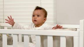 Nettes Baby, das in seiner Krippe sitzt stock video