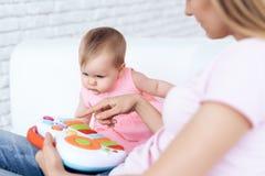Nettes Baby, das Spielzeug auf Sofa mit Mutter spielt stockfoto