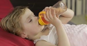 Nettes Baby, das zu Hause auf gem?tlichem Bett und trinkendem Saft von der Flasche schl?ft lizenzfreie stockfotos
